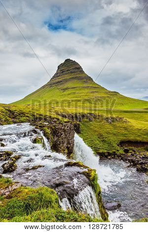 Threaded full-flowing waterfall Kirkyufell Foss on the grassy mountains. Iceland - country of mountains, rivers and waterfalls