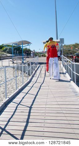 COOGEE,WA,AUSTRALIA-APRIL 3,2016: Lifeguard stilt walkers walking the jetty at the Coogee Beach Festival in Coogee, Western Australia.