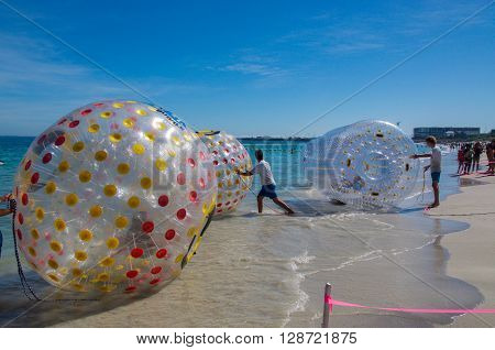 COOGEE,WA,AUSTRALIA-APRIL 3,2016: Coogee Beach Festival with floating inflatable water balls,people and the Indian Ocean waters of Coogee, Western Australia.