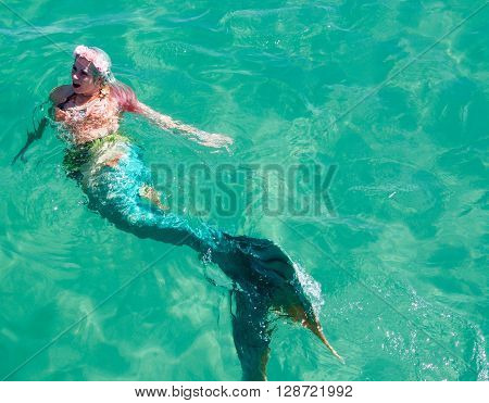 COOGEE,WA,AUSTRALIA-APRIL 3,2016: Mermaid entertainer in costume swimming in the Indian Ocean at the Coogee Beach Festival in Coogee, Western Australia.