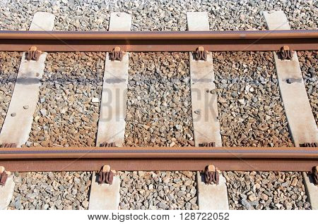 Railway tracks with railroad ties, sleepers and rock bed in closeup detail with rusted metal.