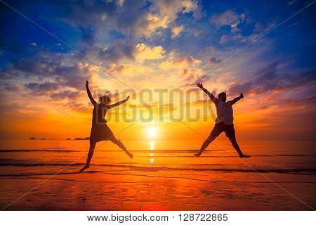 Silhouettes of young people jumping at sunset on the sea beach.