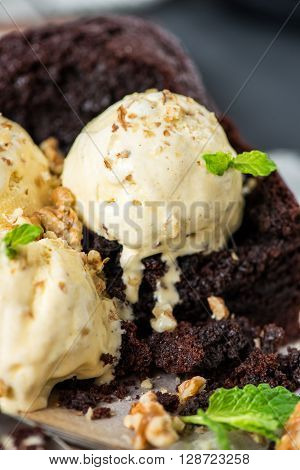 Healthy Vegan Chocolate Loaf (Cake) with Vanilla Ice-Cream Scoops Walnut Pieces and Mint on Dark Grey Background