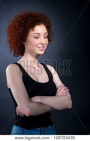 Portrait Of Red-haired Girl Looking Down With Her Hands Crossed On Her Chest