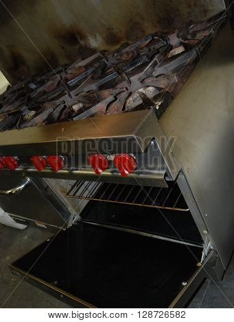 Old but functional commercial gas range and oven with multiple burners.