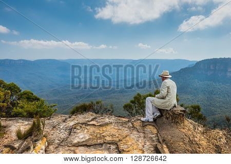 Sydney Australia - November 10 2014: The imposing man in a hat sitting on the edge of a cliff admiring magnificent view of rocks and canyons near Wentworth Falls in the Blue Mountains NSW Australia.