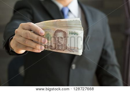 Businessman holding money thai baht in sute a tidy