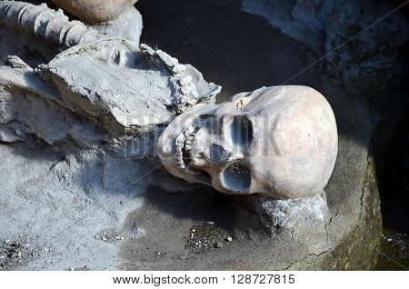skull and skeleton of long time ago dead men in the ruins of Ercolano Italy