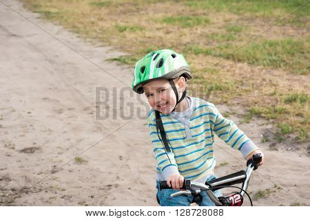 The child riding a bicycle. The kid in a helmet riding a bike in the park. Beautiful baby. Toned image. HDR.