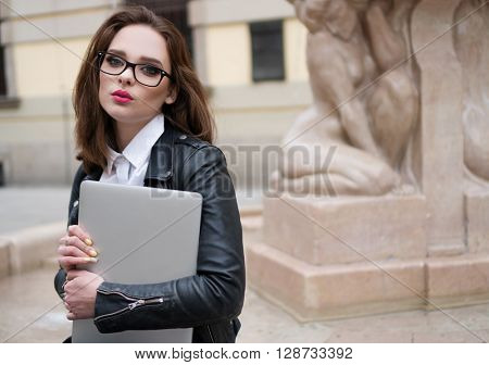 pretty stylish business woman or student with the laptop in the town , wearing glasses