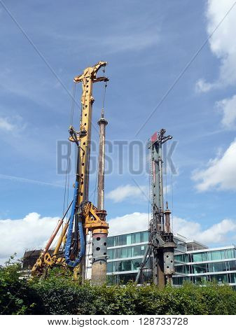 Two drill rigs on the construction site with a modern building in the background