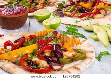 Homemade chicken burritos with vegetables lime and salsa sauce on wooden background full focus studio lights close-up