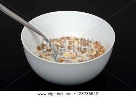 Muesli with a mix of healthy fruit nuts and seeds and milk in a dish against a black background.