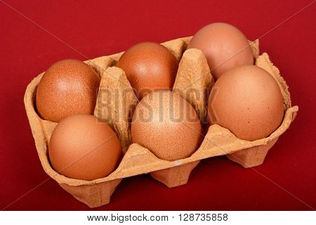 Six fresh brown eggs in a brown cardboard box against a red background.