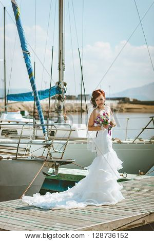 Bride in white wedding dress with a train, stands on the pier in the port
