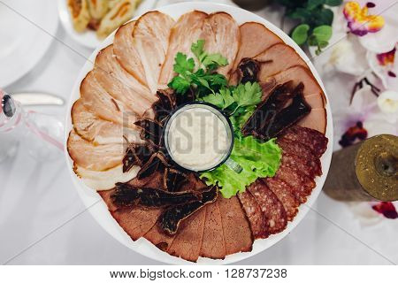 Platter of Assorted Cured Meats. Assorted cold meat platter artistically arranged. Salami, Italian prosciutto. Assorted meat products. A variety of processed cold meat products. Tasty sliced sausage