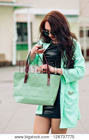 Funny model in sunglasses and in a little green dress, white background. Fashion lifestyle portrait of young happy pretty woman laughing and having fun on the party. favorite music at earphones, stylish vintage outfit, bright fresh colors