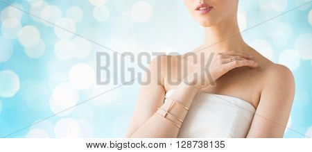 glamour, beauty, jewelry and luxury concept - close up of beautiful woman with golden ring and bracelet over blue holidays lights background