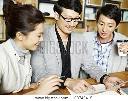 a team of young asian business people working together using tablet computer in office.