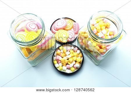 Colorful spiral jelly and colorful marshmallows with glass jars on blue background. Focus on jelly and marshmallows on floor.   Space for texts.