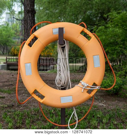 Lifebuoy hanging on a wooden deck. Lifebuoy ring on a wooden deck life saving concept in optimistic bright colors