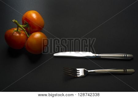 tomatoes and cutlery on a black table