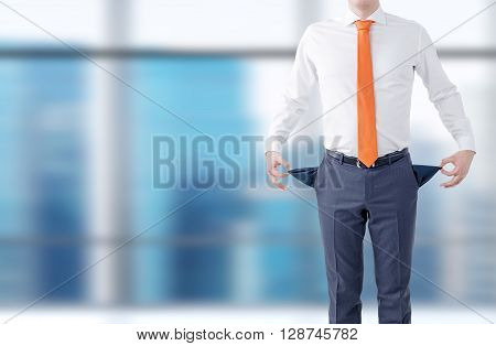 Unemployment concept with businessman showing empty pockets on blurry building background