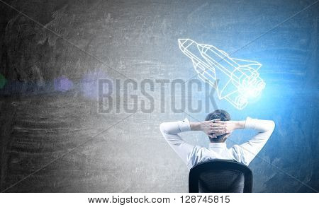 Businessman sitting in front of chalkboard with abstract rocket ship. Start up concept