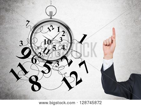 Time management concept with broken clock and businessman putting one finger up on concrete background