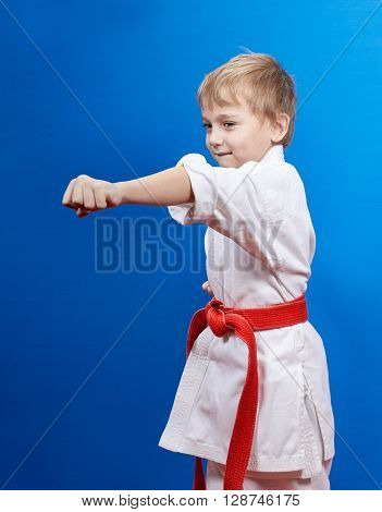 Boy with red belt beats blow arm on the blue background
