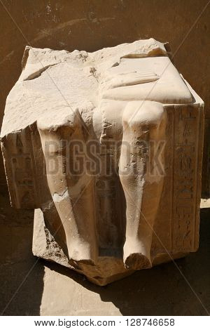 piece of egyptian sculpture carved stone block with knees legs and hieroglyphs in Egypt Africa