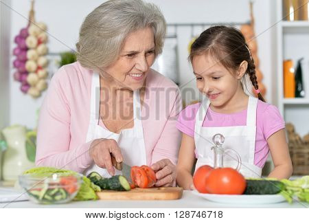 Senior woman with granddaughter cooking in kitchen