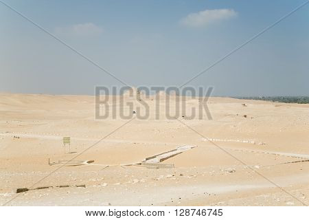 landscape of Egyptian desert with archeological area and far ruined pyramids next to Saqqara in Egypt Africa