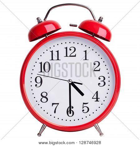 Round red alarm clock shows half past four