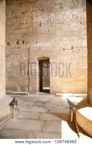 small door stone wall of Egyptian Edfu Temple of falcon god Horus with carving figures and hieroglyphs in Egypt Africa