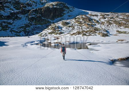 brunette sport active woman with green vest red sweater brown trousers walking hiking in snow with blue sky in Gredos mountain Avila Spain Europe