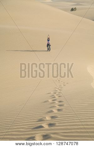 happy woman with blue jeans posing stretching arms up on sand dune looking in Maspalomas desert Gran Canaria Canary Islands Spain Europe