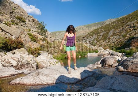 active sport brunette woman purple shirt green short trousers hiking and walking on rock over water pond of river in summer in Gredos Avila Spain Europe