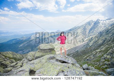 brunette woman with red sweater brown short trousers and sunglasses posing on top rock looking over peaks mountain and valley in Gredos mountain Avila Spain Europe