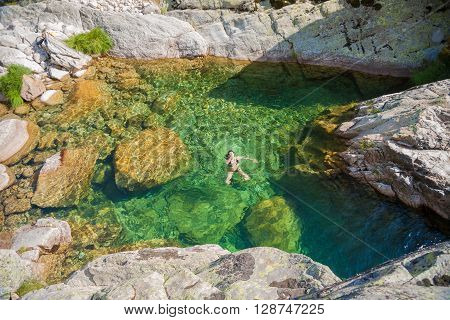 brunette woman purple bikini swimming in green water natural pond of river lake or lagoon in summer in Gredos mountain Avila Spain Europe