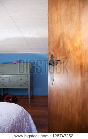 interior house of a mansard room with blue wall and white ceiling open brown wood door with black classic handle and wooden vinyl floor also green retro furniture and white bedspread