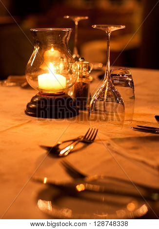 Romantic restaurant table setting of cutlery and glasses