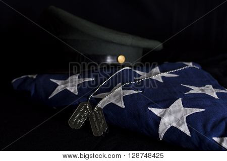 Folded American burial flag with Vietnam era Army hat and dog tags.