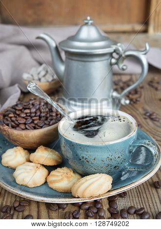 Blue cup of black coffee cookies and coffee pot surrounded by linen cloth sugar pieces and coffee beans on old wooden table