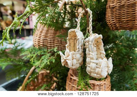 Sandals made of straw ancient traditional russian type of footwear. Natural sandals for baby with a bow.