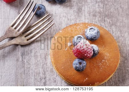 Home-made breakfast or brunch: american style pancakes served with berries and sugar powder, top view