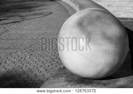 architectural abstract element in the form of the sphere closeup on an indistinct background of a sidewalk stone blocks of monochrome tone