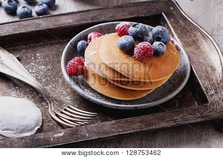 Home-made breakfast or brunch: american style pancakes served with berries and sugar powder on vintage metal tray with a cup of black tea
