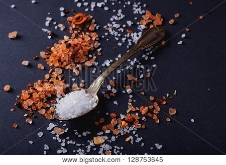 Sifting sea salt  and Himalayan rose rock salt with chili spices in a spoon over black background.