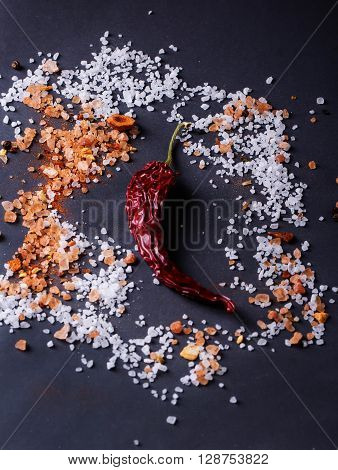 Sifting sea salt  and Himalayan rose rock salt with chili pepper over black background.